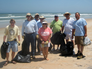 Peoples Gas team members with the Daytona Division with the bags of trash they've filled on Ormond Beach.