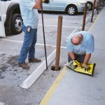 Team members install traffic posts along the ECHO storefront to protect people on the sidewalk from cars.