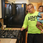 Vu Brown marvels at his new appliances with his granddaughter.