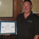 Chris Durost with the recognition from the Department of Defense for Justin Hartley and Peoples Gas.